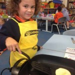 Young child making pancakes.