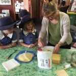 Children being taught how to make pancakes.