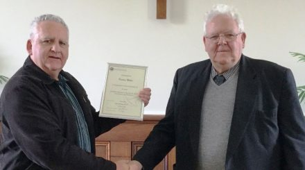 Rev Grahame Abrahams (l) presents Keeton Miles with his service certificate