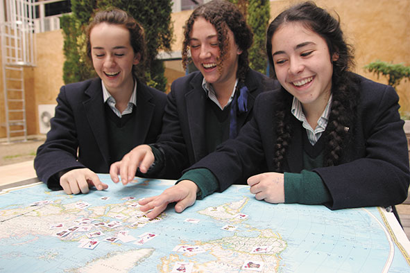 PEGS students Jiana Bivenetto , Emily Fry and Laura D'Aprano locate tax havens on a world map