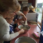 Woman helping children make pancakes