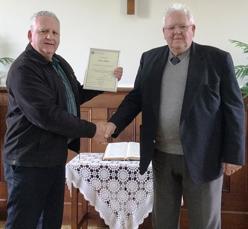 Rev Grahame Abrahams (left) presents Keeton Miles with his service certificate