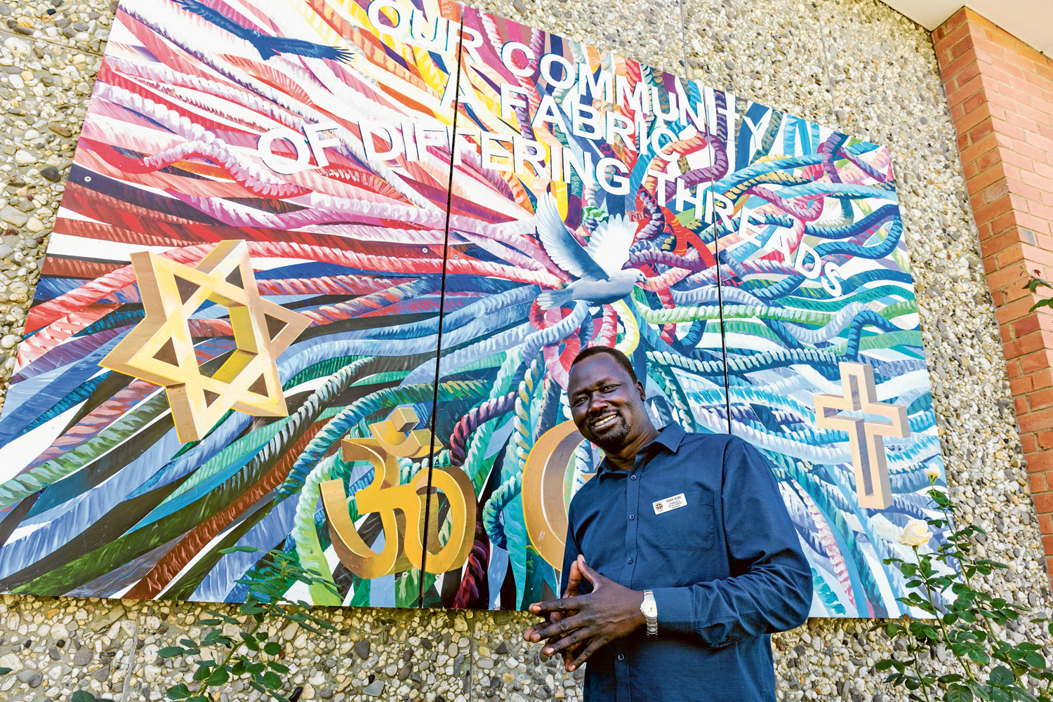 Riak Kiir in front of the mural outside Pakenham Uniting Church