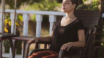 woman-in-black-top-sitting-on-brown-armchair-3331574