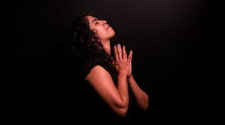 woman praying in shaft of light